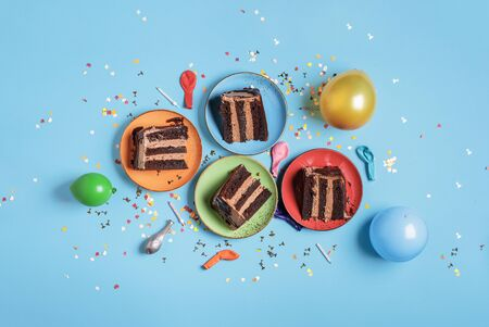 Chocolate birthday cake slices on plates, candles, balloons, and confetti on a blue table. Above view of festive dessert. New year celebration concept Reklamní fotografie