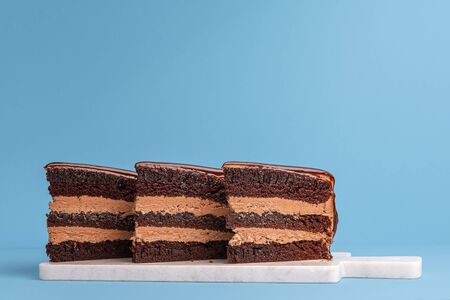 Chocolate layered cake slice aligned and displayed on a white cutting board and blue background. Birthday cake pieces. Three portions of festive cake