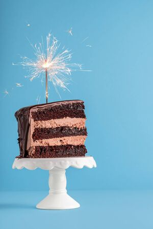 Birthday concept with a slice of chocolate layered cake with a sparkler on top, on a blue table. New year frame with piece of cake with a firework.
