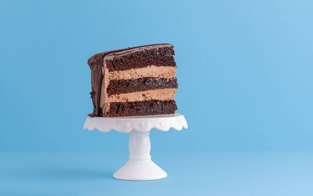 Just one piece of chocolate birthday cake with cocoa frosting, on a white stand and blue background. Minimal piece of cake. Festive layered cake slice Reklamní fotografie