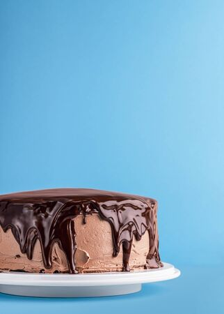 Chocolate cake with dripping melted chocolate on a blue background. Colorful birthday cake frame. Homemade chocolate dessert. Chocolate glazed cake. Reklamní fotografie