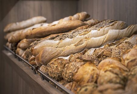 Bread mix on wooden shelves. Bakery goods displayed on a shelf. Various types of loaves. Freshly baked crusty breads. Appetizing french bread.