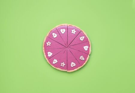 Christmas Advent context with a pink chocolate pie slices with numbers on it. Chocolate tart on green table. Numbered pie slices. Limited pie pieces.