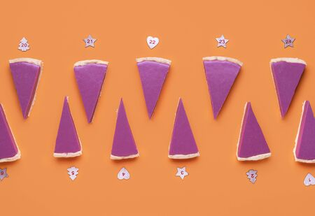 Christmas Advent calendar with ruby chocolate pie slices and numbers on orange background. Pink pie slices pattern. Christmas dessert background. Banque d'images