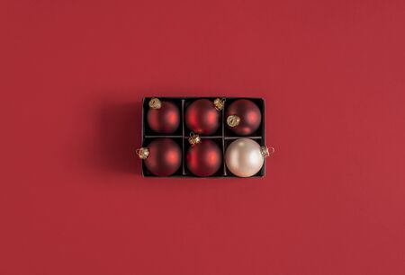 Red Christmas baubles and just one different, a white Xmas ball, in a black box, on a red background. Minimal image with Christmas ornaments. Flat lay