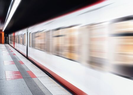 Subway train in motion and an empty subway platform. Public transportation context. Eco-friendly means of transportation. Underground high-speed train
