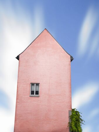 Coral colored building tower with one window against a blue sky. German old house, tall, with just one window, isolated. Minimal surreal architecture.