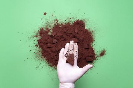 Piece of chocolate held in hand with glove over pile of cacao powder, on green background. Confectionery context. Making chocolate. Dessert ingredient