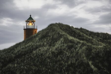 Illuminated orange lighthouse on a high hill with marram grass and moss, on Sylt island, at North Sea, Germany. Brickstone beacon on northern Europe.
