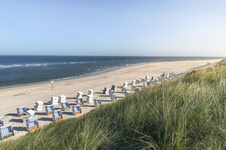 Summer beach landscape with wicker chairs, high grass dunes, and the North Sea water, on Sylt island, Germany. Sunny summer vacation context. 스톡 콘텐츠