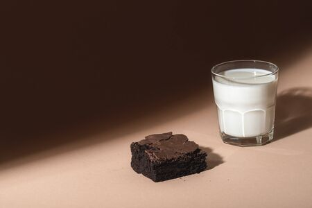 Chocolate brownie cake and a glass of warm milk on a brown background, in sunlight. Indulgence food. Chocolate dessert and milk. Unhealthy breakfast.