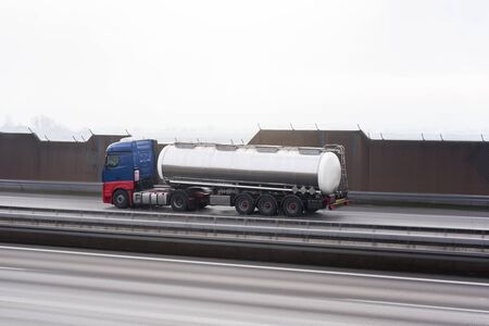 Cistern driving on the highway, near Stuttgart, Germany. Truck with reservoir. Tank truck moving fast on empty highway. Motion blur road and cistern