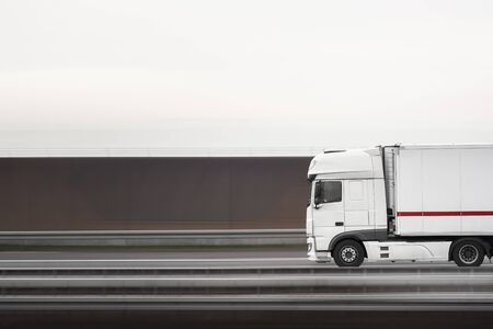 Truck vehicle moving fast on the highway, near Stuttgart, Germany. Selective focus logistic vehicle. White truck in motion. Freight transport vehicle Stock Photo