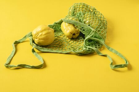 Fresh quince fruits in a net fabric bag on yellow background. Eco-friendly shopping bag and fruits. Reusable grocery bag. Reduce plastic pollution. Reklamní fotografie