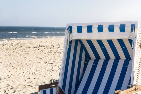 Wicker chair close-up with blue strips on a sandy beach at the North Sea, on Sylt island, Germany. Sunny summer beach day with sun and seawater.