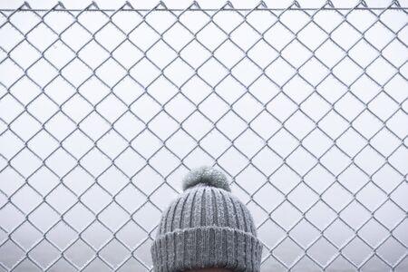Cappello innevato sulla testa di una donna in una fredda giornata di gennaio. Primo piano solo del cappello invernale. Sfondo di recinzione di filo congelato