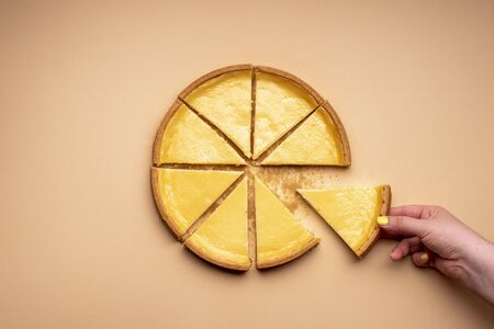 Woman's hand grabbing a piece of cheesecake. Sliced cheese tart on a yellowish background. Pie sliced in equal parts.