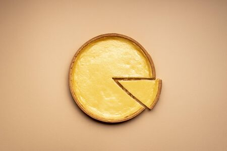 Delicious cheesecake on a cream-colored table, above view. Single piece of cheese tart sliced from the whole. Homemade sweet food. Famous cheese dessert