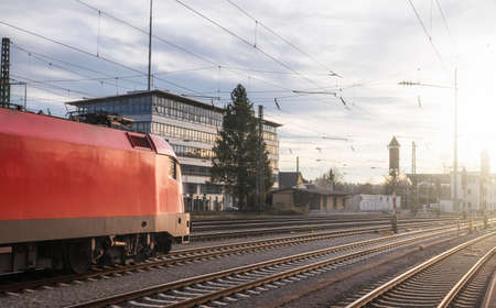 Modern red locomotive traveling on railway tracks. Public transport. Train travel concept. High-speed locomotive near Singen train station, Germany.
