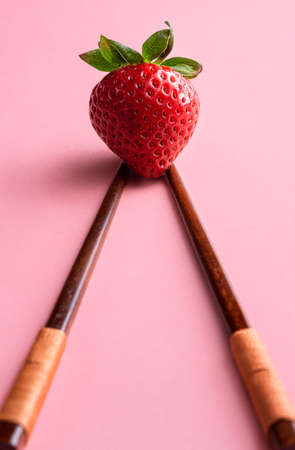 Organic strawberry on Asian chopsticks on pink background. Sweet summer fruit. One strawberry on pink seamless background. Delicious healthy dessert.