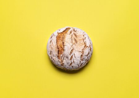 Freshly baked sourdough bread on a yellow seamless background. Wheat loaf without yeast flat lay. Traditional rustic bread.