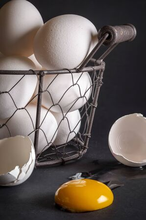Close-up of a basket full of chicken eggs. Cracked eggshell and egg yolk in the foreground. Concept image for the proverb: don't put all your eggs in one basket