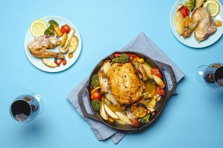 Roasted chicken with vegetables and two glasses of red wine. Chicken and vegetables baked in an iron cast. Roasted chicken with vegetables in blue plates