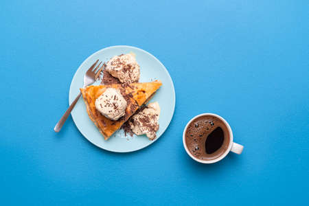 Apple pie slice with golden crust served with vanilla ice cream and a hot coffee on a blue table. Flat lay with an apple tart. Thanksgiving dessert. 写真素材