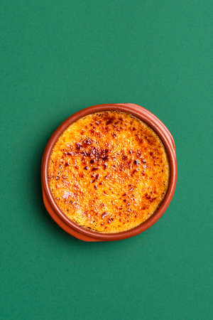 Homemade creme brulee with caramel crust, in a clay tray, on green seamless background. French custard cake. Burnt cream with caramelized brown sugar