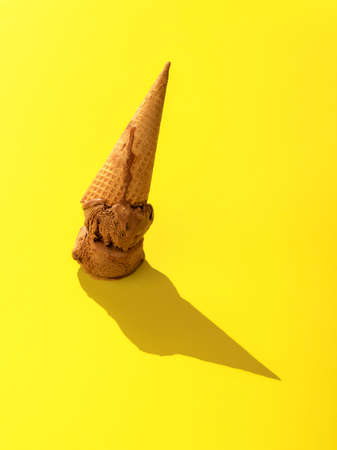 Waffle cone ice cream upside down on a yellow background. Close-up with a chocolate ice cream in bright light.