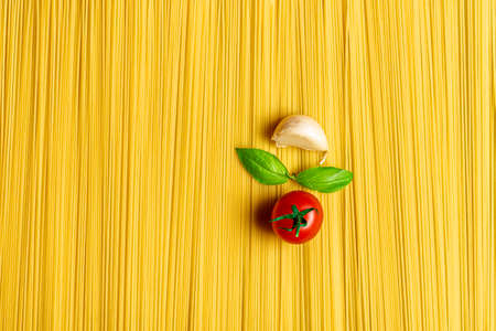 Flat lay with raw spaghetti and the ingredients for the traditional Italian tomato sauce. Abstract background with a pile of uncooked spaghetti