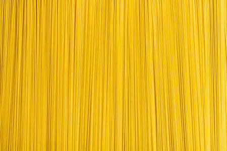 Above view with a pile of uncooked yellow spaghetti. Abstract background with raw pasta. 스톡 콘텐츠