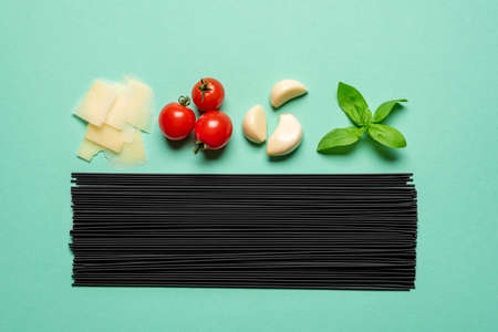 Uncooked black spaghetti and the ingredients for a tomato sauce, top view on a green table. Raw ingredients for a delicious italian meal, spaghetti with tomato sauce.