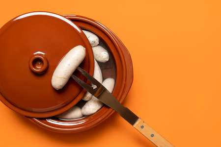 Boiled weisswurst, german white sausage cooked in a ceramic pot, on orange background. Top view of bavarian veal sausage. Germany national food.