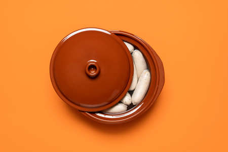 Boiled white sausage in a brown pot, isolated on orange background. Top view of Bavarian veal sausage in water. German traditional weisswurst.