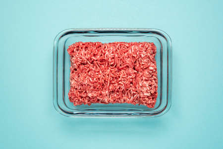 Above view with ground beef in a glass food container on a blue colored table. Ground beef in a glass dish isolated on a blue background. Reklamní fotografie