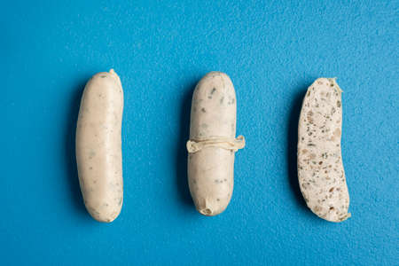 White sausages presentation with peeled skin and wurst section isolated on a blue table. Top view of boiled veal sausages. Bavarian traditional food. Reklamní fotografie