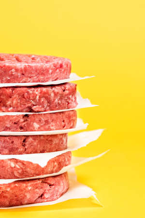 Close-up with a stack of burger patties against a yellow-colored background. Raw beef burger patties one above other on a yellow table. Reklamní fotografie