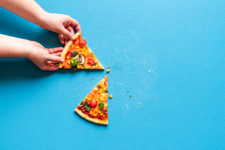 Woman's hand grabbing a slice of vegetarian pizza. Above view with slices of pizza primavera on a blue colored table. Reklamní fotografie