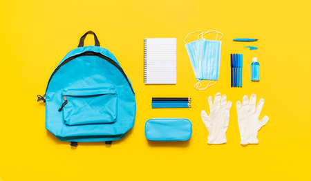 Back to school in pandemic concept. School supplies, an empty school bag and protective equipment, masks, gloves and sanitizer. New normal in school. Reklamní fotografie