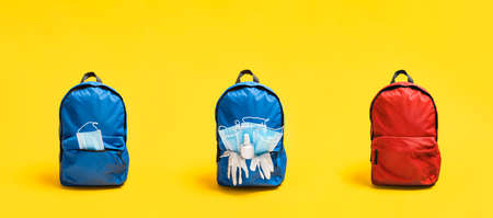 School in pandemic concept with school bags equipped with face masks, surgical gloves and hand sanitizer, isolated on yellow background.
