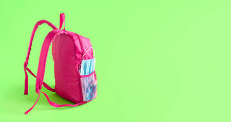 School in pandemic concept. Pink schoolbag with medical masks and hand sanitizer, isolated on green background. New normal in school and travel.