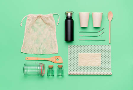 Sustainability concept top view. Reusable organic shopping bag, coffee cup and beeswax cloth, isolated on green background. Environmental safe objects