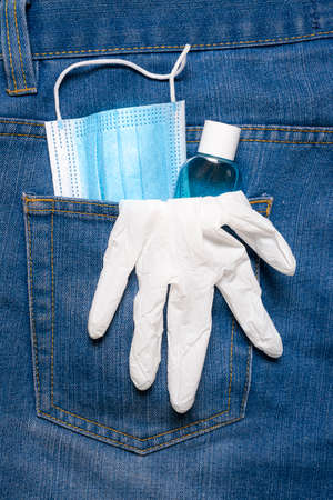 Jeans pocket with a protective mask, hand sanitizer, and surgical gloves. New normal concept. Lifestyle after COVID. Protection against coronavirus. Reklamní fotografie