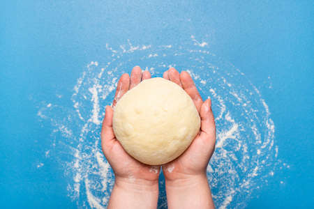 Woman holding dough in hand over a blue background. Top view of uncooked dough. Baking at home concept. Handmade donut batter. Leavened sourdough. Reklamní fotografie