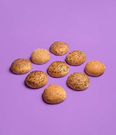 Bread buns symmetrically aligned and isolated on seamless purple background. Hamburger buns with golden crust. Bread rolls with sesame and poppy seed.