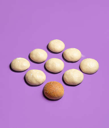 Baking bread buns concept with raw dough balls and one baked hamburger bun, isolated on a purple background. Symmetrically displayed dough buns.