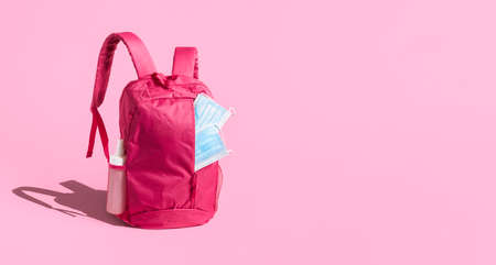 School reopening in the pandemic banner. Pink schoolbag with medical masks, isolated on pink background. First day of school. Travel in the pandemic.