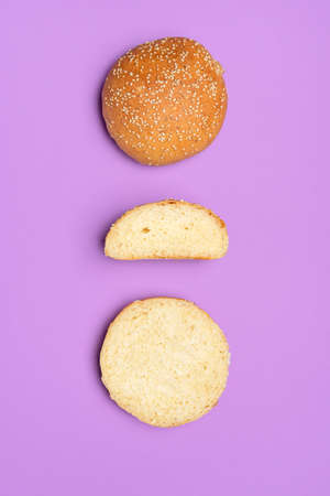 Homemade bread buns section, isolated on a purple background. Flat lay with burger bread cut in half. Hamburger rolls with sesame seeds.