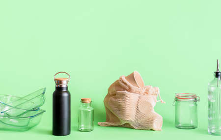 Sustainable lifestyle concept with glass objects,   biodegradable coffee cups, isolated on green background. Plastic-free household products Reklamní fotografie